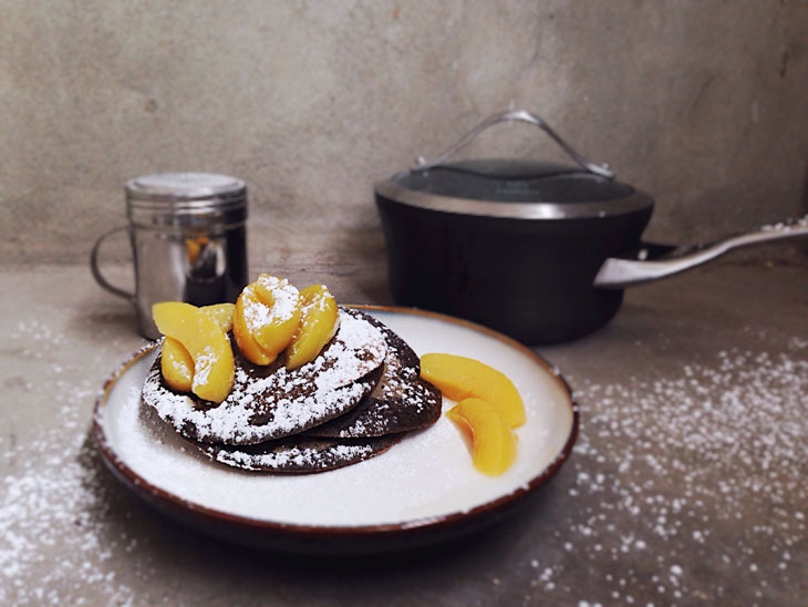 Buckwheat pancakes with peaches and powdered sugar